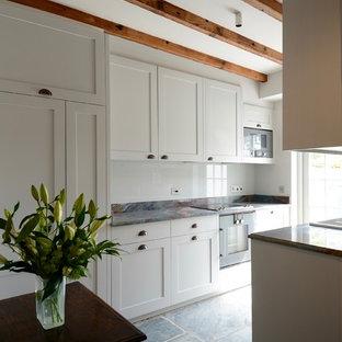 コーンウォールの中サイズのラスティックスタイルのおしゃれなキッチン (エプロンフロントシンク、シェーカースタイル扉のキャビネット、白いキャビネット、大理石カウンター、マルチカラーのキッチンパネル、ガラス板のキッチンパネル、シルバーの調理設備の、スレートの床、アイランドなし) の写真