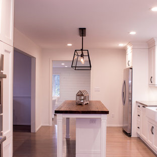 Kitchen appliance - Galley medium tone wood floor and brown floor kitchen photo in New York with a farmhouse sink, white cabinets, concrete countertops, red backsplash, brick backsplash, stainless steel appliances and an island