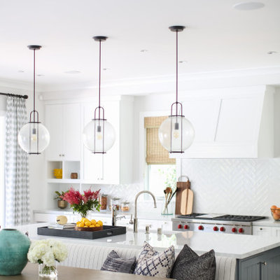 Eat-in kitchen - large transitional galley brown floor eat-in kitchen idea in Orange County with an undermount sink, shaker cabinets, white cabinets, white backsplash, stainless steel appliances, an island and white countertops