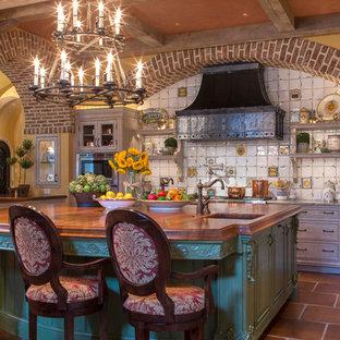 Geschlossene, Große Mediterrane Küche in L-Form mit Küchenrückwand in Weiß, Unterbauwaschbecken, profilierten Schrankfronten, grauen Schränken, Kupfer-Arbeitsplatte, Rückwand aus Keramikfliesen, Küchengeräten aus Edelstahl, Terrakottaboden und Kücheninsel in Miami