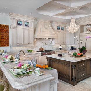 Immagine di una grande cucina ad U mediterranea con lavello a doppia vasca, ante in legno chiaro, top in granito, paraspruzzi beige, paraspruzzi in lastra di pietra, elettrodomestici da incasso, pavimento in marmo e isola