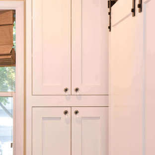 Photo of a large l-shaped kitchen pantry in New York with a submerged sink, shaker cabinets, white cabinets, engineered stone countertops, white splashback, stainless steel appliances and no island.