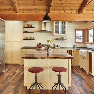 Réalisation d'une cuisine marine avec un évier intégré, un placard à porte shaker, un îlot central et un plan de travail gris.