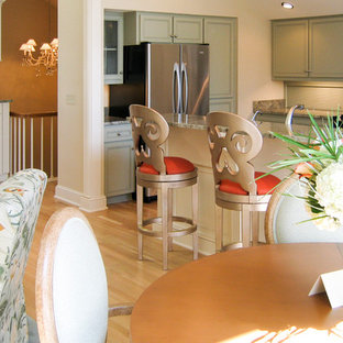Photo of a transitional u-shaped open plan kitchen in Cleveland with a triple-bowl sink, beaded inset cabinets, green cabinets, granite benchtops, beige splashback, ceramic splashback, stainless steel appliances, light hardwood floors and a peninsula.