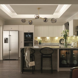 Mid-sized transitional open concept kitchen appliance - Inspiration for a mid-sized transitional u-shaped dark wood floor and brown floor open concept kitchen remodel in Dublin with a double-bowl sink, flat-panel cabinets, beige cabinets, concrete countertops, multicolored backsplash, limestone backsplash, black appliances and a peninsula