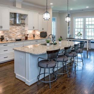 Zweizeilige Klassische Küche mit Unterbauwaschbecken, Schrankfronten im Shaker-Stil, weißen Schränken, Küchenrückwand in Beige, Küchengeräten aus Edelstahl, braunem Holzboden, Kücheninsel und Rückwand aus Schiefer in Wilmington