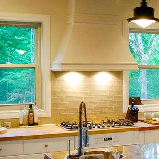 モントリオールの中くらいのカントリー風おしゃれなキッチン (ドロップインシンク、フラットパネル扉のキャビネット、白いキャビネット、大理石カウンター、ベージュキッチンパネル、サブウェイタイルのキッチンパネル、白い調理設備) の写真