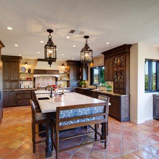 ラスベガスのサンタフェスタイルのおしゃれなキッチン (エプロンフロントシンク、シェーカースタイル扉のキャビネット、濃色木目調キャビネット、ベージュキッチンパネル、パネルと同色の調理設備、テラコッタタイルの床、赤い床、茶色いキッチンカウンター) の写真