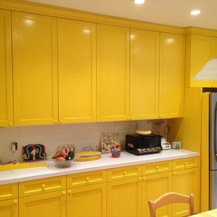 ニューヨークの中くらいのコンテンポラリースタイルのおしゃれなキッチン (落し込みパネル扉のキャビネット、黄色いキャビネット、珪岩カウンター、シルバーの調理設備、淡色無垢フローリング) の写真