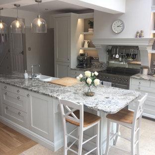ウエストミッドランズのサンタフェスタイルのおしゃれなアイランドキッチン (エプロンフロントシンク、シェーカースタイル扉のキャビネット、白いキャビネット、御影石のキッチンパネル、ライムストーンの床) の写真