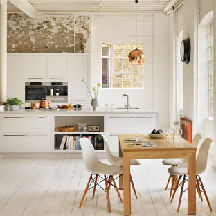 Contemporary kitchen/diner in London with an island, painted wood flooring, a submerged sink, flat-panel cabinets, white cabinets, engineered stone countertops and stainless steel appliances.