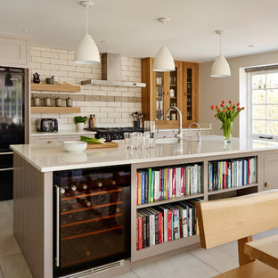 Example Of A Clic Kitchen Design In London With An Island And Beige Cabinets