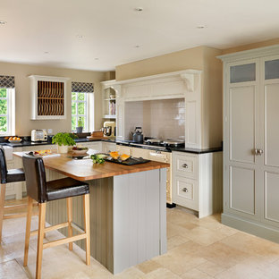 This is an example of a traditional l-shaped kitchen in London with coloured appliances and an island.