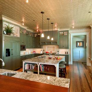 Imagen de cocina comedor en L, clásica, con armarios con paneles empotrados, puertas de armario verdes, electrodomésticos con paneles, fregadero de un seno y encimera de granito