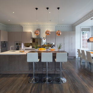 Inspiration for a contemporary l-shaped kitchen/diner in London with a submerged sink, flat-panel cabinets, beige cabinets, integrated appliances, dark hardwood flooring and an island.