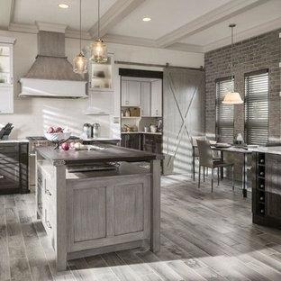 タンパの広いトランジショナルスタイルのおしゃれなキッチン (アンダーカウンターシンク、シェーカースタイル扉のキャビネット、ヴィンテージ仕上げキャビネット、白いキッチンパネル、カラー調理設備、淡色無垢フローリング、御影石カウンター、サブウェイタイルのキッチンパネル、グレーの床) の写真