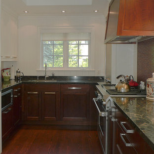Mid-sized traditional enclosed kitchen remodeling - Example of a mid-sized classic u-shaped dark wood floor enclosed kitchen design in Toronto with an undermount sink, shaker cabinets, dark wood cabinets, recycled glass countertops, red backsplash, stone tile backsplash, stainless steel appliances and no island