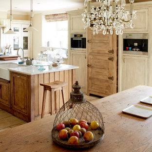 Diseño de cocina comedor en L, romántica, de tamaño medio, con fregadero sobremueble, armarios con paneles empotrados, una isla y suelo beige