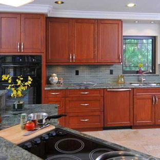 Exempel på ett mellanstort modernt kök, med en dubbel diskho, skåp i shakerstil, skåp i mellenmörkt trä, granitbänkskiva, grått stänkskydd, stänkskydd i glaskakel, svarta vitvaror, kalkstensgolv, en halv köksö och beiget golv