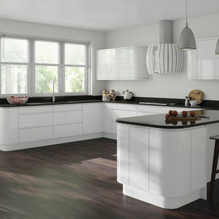Photo of a large contemporary u-shaped kitchen/diner in Buckinghamshire with a submerged sink, flat-panel cabinets, white cabinets, onyx worktops, black splashback, dark hardwood flooring and a breakfast bar.