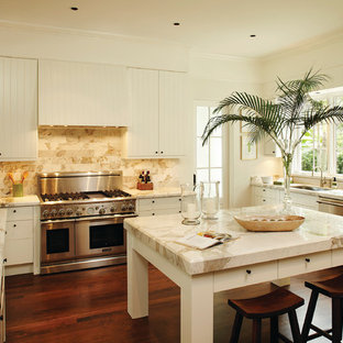 Mid-sized tropical eat-in kitchen pictures - Mid-sized island style single-wall dark wood floor and brown floor eat-in kitchen photo in Miami with an undermount sink, white cabinets, marble countertops, multicolored backsplash, marble backsplash, stainless steel appliances and an island