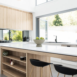 Contemporary l-shaped kitchen in Brisbane with a drop-in sink, flat-panel cabinets, white cabinets, window splashback, stainless steel appliances, with island and grey floor.