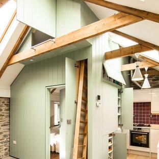 Modelo de cocina comedor en L, de estilo de casa de campo, pequeña, con armarios con paneles lisos, puertas de armario verdes, suelo de madera clara, salpicadero rojo y salpicadero de azulejos de cerámica