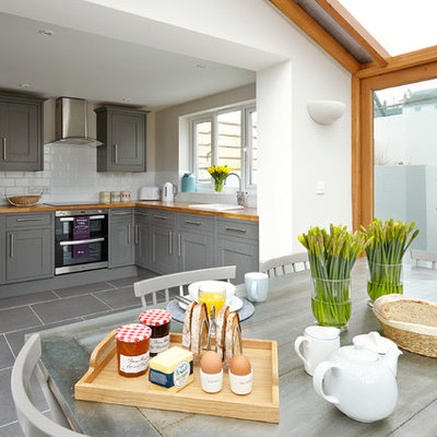 Example of a beach style gray floor eat-in kitchen design in London with a drop-in sink, shaker cabinets, gray cabinets, wood countertops, white backsplash, subway tile backsplash, stainless steel appliances and no island