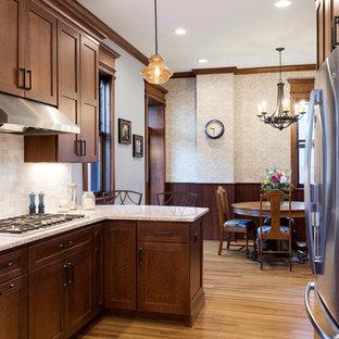 Große Urige Wohnküche in U-Form mit Unterbauwaschbecken, hellbraunen Holzschränken, Quarzwerkstein-Arbeitsplatte, Rückwand aus Marmor, Küchengeräten aus Edelstahl, hellem Holzboden, Halbinsel, gelbem Boden, Schrankfronten im Shaker-Stil und Küchenrückwand in Weiß in Minneapolis