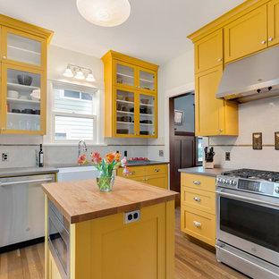 ポートランドの広いトラディショナルスタイルのおしゃれなキッチン (エプロンフロントシンク、シェーカースタイル扉のキャビネット、黄色いキャビネット、クオーツストーンカウンター、サブウェイタイルのキッチンパネル、シルバーの調理設備、グレーのキッチンカウンター、白いキッチンパネル、淡色無垢フローリング) の写真