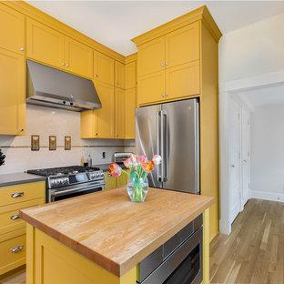 Geschlossene, Große Urige Küche in U-Form mit Landhausspüle, Schrankfronten im Shaker-Stil, gelben Schränken, Quarzwerkstein-Arbeitsplatte, bunter Rückwand, Rückwand aus Metrofliesen, Küchengeräten aus Edelstahl, hellem Holzboden, Kücheninsel und grauer Arbeitsplatte in Portland