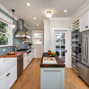 Traditional kitchen designs - Elegant galley kitchen photo in Portland with a farmhouse sink, shaker cabinets, white cabinets, wood countertops, gray backsplash, subway tile backsplash, stainless steel appliances and an island