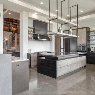 Große Moderne Küche in U-Form mit Vorratsschrank, Waschbecken, flächenbündigen Schrankfronten, grauen Schränken, Kalkstein-Arbeitsplatte, Küchenrückwand in Weiß, Rückwand aus Porzellanfliesen, schwarzen Elektrogeräten, Betonboden, zwei Kücheninseln, grauem Boden, schwarzer Arbeitsplatte und eingelassener Decke in Portland