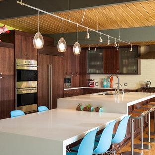 Bild på ett 50 tals vit vitt kök, med en undermonterad diskho, släta luckor, skåp i mörkt trä, rostfria vitvaror, korkgolv, bänkskiva i kvartsit, vitt stänkskydd, stänkskydd i keramik och en köksö