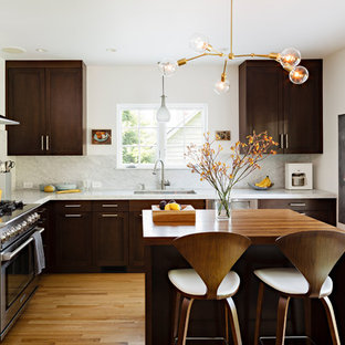 Enclosed kitchen - mid-sized contemporary l-shaped medium tone wood floor enclosed kitchen idea in Portland with wood countertops, stainless steel appliances, shaker cabinets, dark wood cabinets, white backsplash, stone slab backsplash and an undermount sink