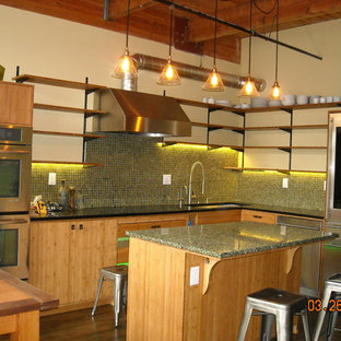 Photo of an industrial eat-in kitchen in Portland with an undermount sink, flat-panel cabinets, light wood cabinets, recycled glass benchtops, green splashback, glass sheet splashback, stainless steel appliances, dark hardwood floors and with island.