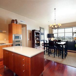 ポートランドの小さいアジアンスタイルのおしゃれなキッチン (フラットパネル扉のキャビネット、中間色木目調キャビネット、人工大理石カウンター、白いキッチンパネル、シルバーの調理設備、濃色無垢フローリング、赤い床) の写真