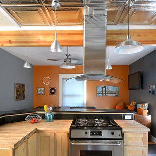 ポートランドの中サイズのインダストリアルスタイルのおしゃれなキッチン (ダブルシンク、シェーカースタイル扉のキャビネット、淡色木目調キャビネット、ソープストーンカウンター、黒いキッチンパネル、石スラブのキッチンパネル、シルバーの調理設備の、リノリウムの床) の写真
