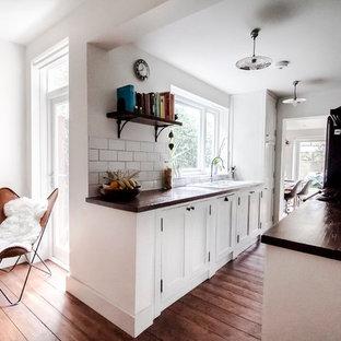 ロンドンの中サイズのインダストリアルスタイルのおしゃれなキッチン (シングルシンク、シェーカースタイル扉のキャビネット、白いキャビネット、木材カウンター、白いキッチンパネル、サブウェイタイルのキッチンパネル、黒い調理設備、濃色無垢フローリング、茶色い床) の写真
