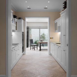 Medium sized traditional galley kitchen pantry in London with a submerged sink, shaker cabinets, white cabinets, limestone worktops, limestone splashback, integrated appliances, medium hardwood flooring, no island and brown floors.