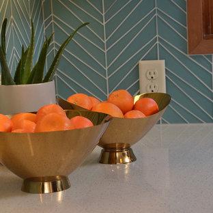 ポートランドの中サイズのミッドセンチュリースタイルのおしゃれなキッチン (アンダーカウンターシンク、フラットパネル扉のキャビネット、中間色木目調キャビネット、クオーツストーンカウンター、青いキッチンパネル、ガラスタイルのキッチンパネル、シルバーの調理設備の、淡色無垢フローリング、白いキッチンカウンター) の写真