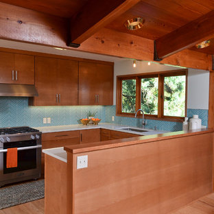 Design ideas for a mid-sized midcentury u-shaped eat-in kitchen in Portland with an undermount sink, flat-panel cabinets, medium wood cabinets, quartz benchtops, blue splashback, glass tile splashback, stainless steel appliances, light hardwood floors, a peninsula and white benchtop.