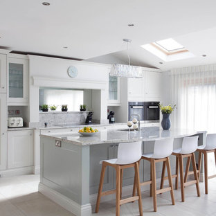 Large transitional l-shaped open plan kitchen in Dublin with an integrated sink, shaker cabinets, blue cabinets, granite benchtops, multi-coloured splashback, stone slab splashback, black appliances, ceramic floors and with island.