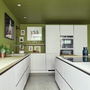 Идея дизайна: угловая кухня среднего размера в современном стиле с белыми фасадами, деревянной столешницей, островом, белым полом, накладной раковиной, плоскими фасадами, зеленым фартуком, черной техникой и полом из терраццо