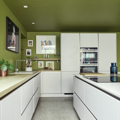 Inspiration for a mid-sized contemporary l-shaped white floor and terrazzo floor kitchen remodel in Dublin with white cabinets, wood countertops, an island, a drop-in sink, flat-panel cabinets, green backsplash and black appliances