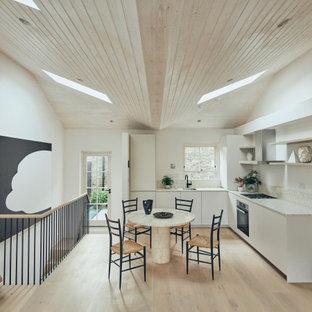 ロンドンの中くらいのコンテンポラリースタイルのおしゃれなキッチン (フラットパネル扉のキャビネット、白いキャビネット、シルバーの調理設備、淡色無垢フローリング、アイランドなし、ベージュの床、ベージュのキッチンカウンター、一体型シンク、テラゾーカウンター、ベージュキッチンパネル、石タイルのキッチンパネル) の写真