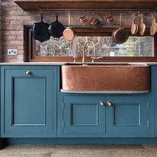 ダブリンの中くらいのインダストリアルスタイルのおしゃれなキッチン (エプロンフロントシンク、シェーカースタイル扉のキャビネット、青いキャビネット、クオーツストーンカウンター、黒い調理設備、濃色無垢フローリング、グレーのキッチンカウンター) の写真