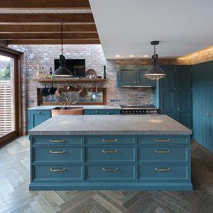 Modelo de cocina comedor industrial, de tamaño medio, con fregadero sobremueble, armarios estilo shaker, puertas de armario azules, encimera de cuarzo compacto, electrodomésticos negros, suelo de madera oscura, una isla y encimeras grises