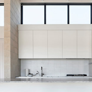 Photo of a contemporary galley kitchen in Melbourne with flat-panel cabinets, white cabinets, yellow splashback, with island, grey benchtop, exposed beam and wood.
