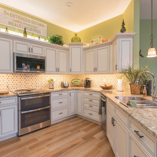 Photo of a small tropical u-shaped kitchen in Other with an undermount sink, white cabinets, granite benchtops, multi-coloured splashback, stone tile splashback, stainless steel appliances, porcelain floors, a peninsula, brown floor and recessed-panel cabinets.